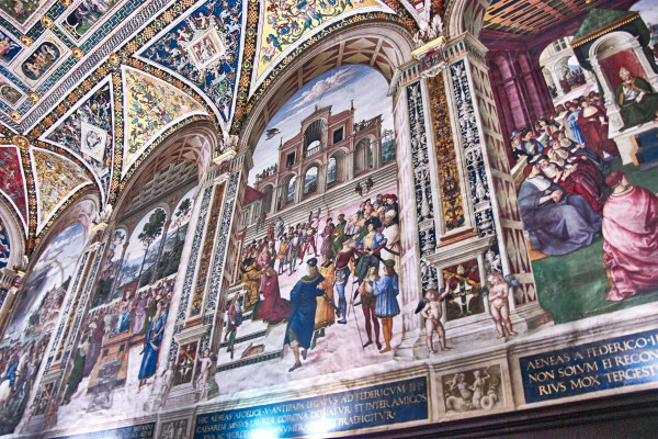 The frescoes show scenes from the Life of Pope Pius II on three Library's walls.