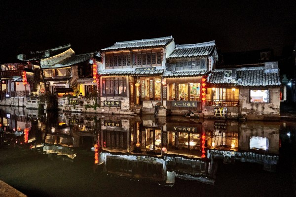 Illuminated buildings along the canal in Xitang