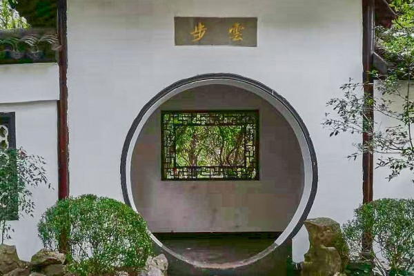A typical round door leads to another garden section