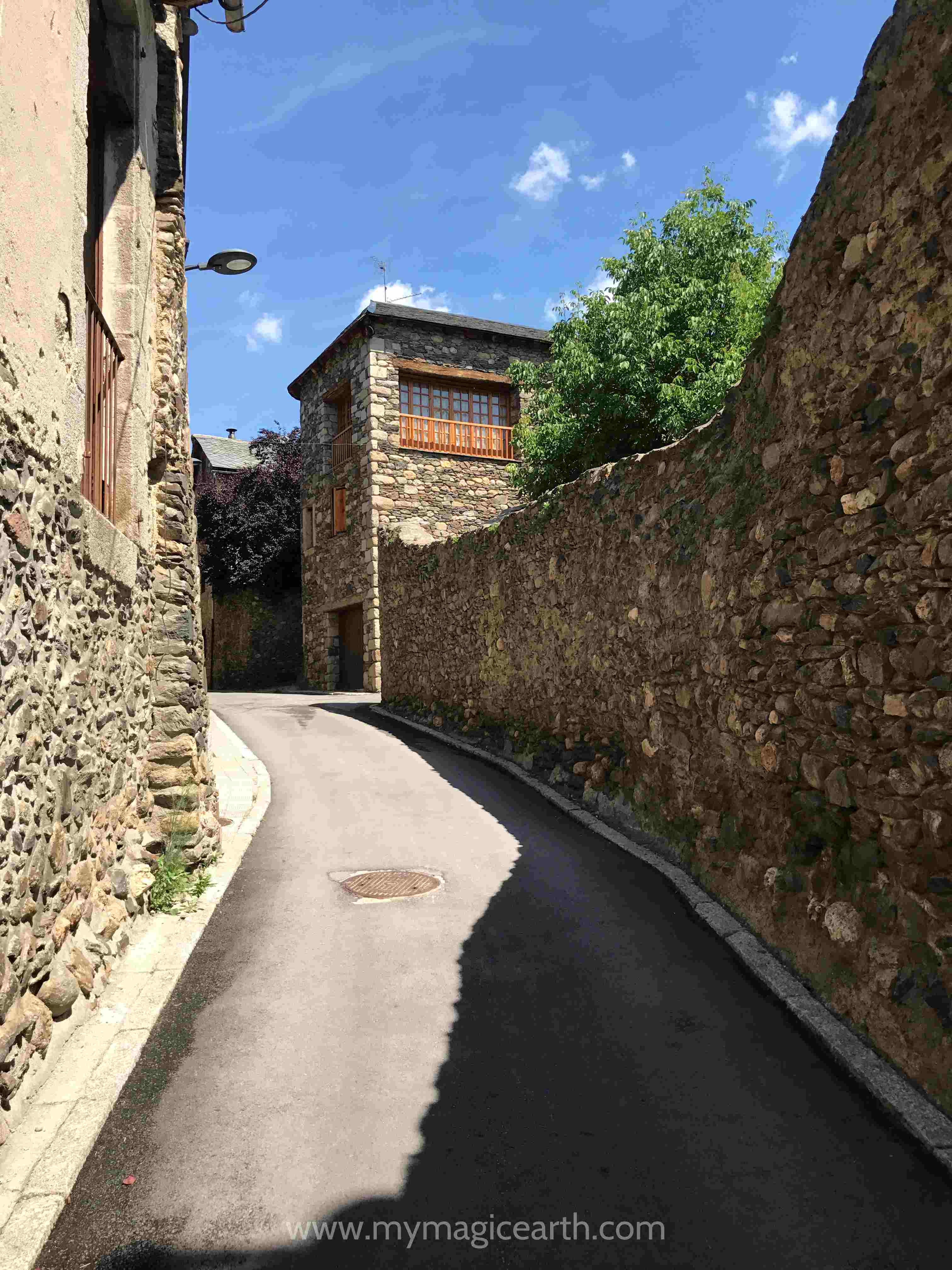 Narrow street between the stone walls in Llivia, Spain