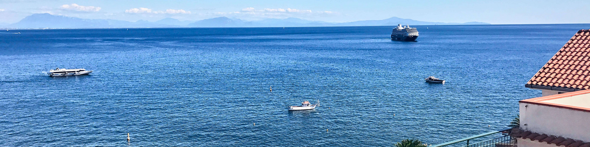 Far out to sea, a sheer white cruise ship was waiting for the passengers from its tender boat.