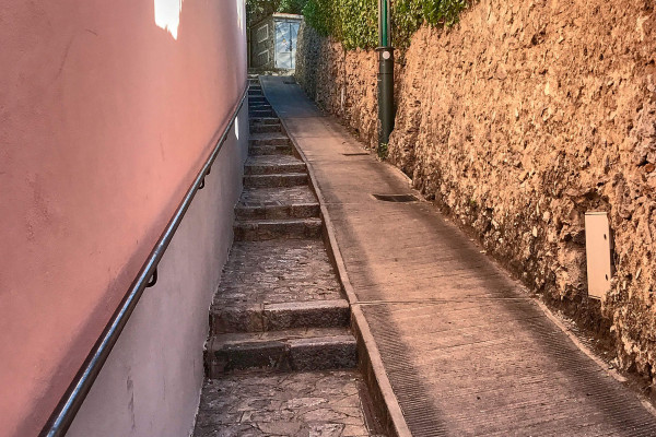 The flat part is the street for a type of narrow carts. Local hotels use those carts to deliver such as goods and luggage.