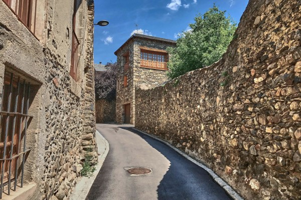 Narrow street between the stone walls in Llivia, Spain